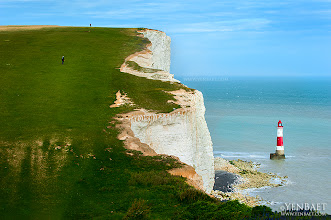 Photo: The Lighthouse on the Bottom of the Cliff of Beachy Head - Eastbourne, UK.  Famous for being the highest chalk sea cliff in Britain, the cliff of Beachy Head is also infamous for being one of the most notorious suicide spots in the world. Just a few days before my visit to this location, another life has been lost. The white cliff rises to 162 meters or 530 ft. above sea level. On a clear day in England, which means never if you're a pessimist, the peak allows views of the southeast coast from Dungeness to the east, to Selsey Bill in the west. The cliff of Beach Head is also a popular setting for music videos, TV shows and movies such as Harry Potter and the Goblet of Fire and James Bond's The Living Daylights.  #BeachyHead   #Eastbourne   #England   #UK   #Travel  #Photography   © Yen Baet - www.YenBaet.com. All Rights Reserved. Join me on Facebook at www.facebook.com/YenBaetPhotography.