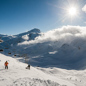Skiers on a slope by Max Mayorov - Landscapes Mountains & Hills ( ray, europe, mountain, peak, valley, recreation, people, sun, alpine, city, elevator, sky, slope, chair lift, shadow, sunny, snow, above, resort, france, alps, ski, direct, building, extreme, support, val claret, tignes, cable, cloudscape, sport, skier, holiday, chair, vacation, european, winter, from the top, season, stand, ski resort, lift, cloud, down, summit, town, small )