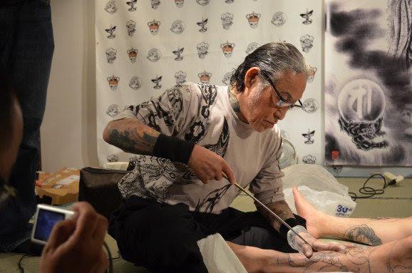 El maestro tatuador realiza su trabajo con baras de Bambu con agujas en la punta.