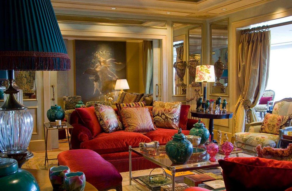 Sala com sofá vermelho, alomofadas coloridas, abajur azul e acessórios para enfeite.
