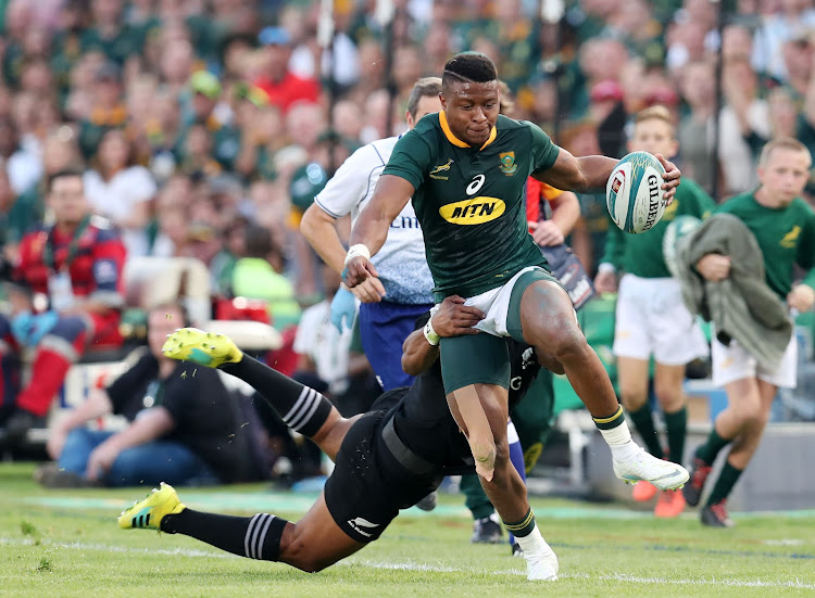 Aphiwe Dyantyi of South Africa powers through a tackle from Waisake Naholo of New Zealand during the Rugby Championship match between the Springboks and the All Blacks at Loftus Stadium in Pretoria on October 6, 2018.