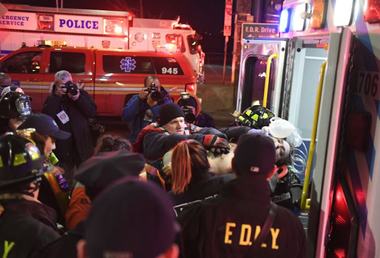 Paramedics and members of the FDNY perform CPR on a victim of a helicopter that crashed into the East River in New York, U.S., March 11, 2018.