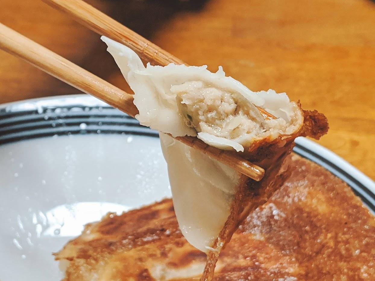 大阪王将餃子1個を箸上げして断面を見せている画像