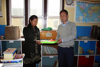 Photo: Shobha handing over the games to Dorje Sir of Chilaune School.