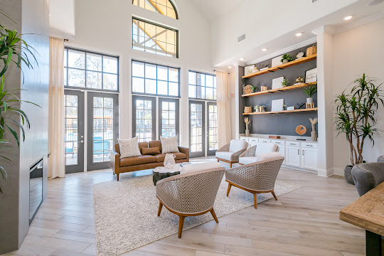 Upscale community clubhouse with modern decor, plush seating, high ceilings with windows, and a fireplace