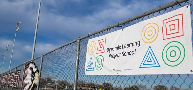 Et banner med teksten «Dynamic Learning Project School» på et skolegjerde.
