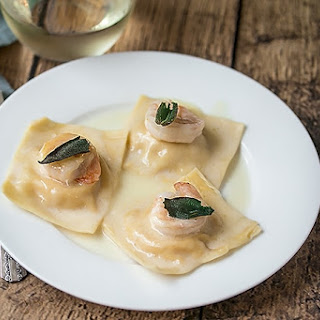 Fresh Butternut Squash Ravioli with Prawns, Fried Sage and Truffle Oil Sauce.
