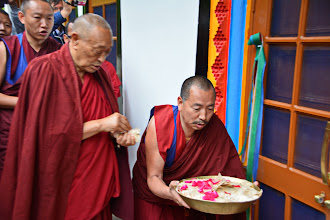 Photo: After the five colored ribbons were untied by His Holiness Menri Trizen Rinpoche and Jetsun Ma, blessed rice with flower petals were used to purify the site as participants followed HH, walked through the Sowa Rigpa Medical Institute.