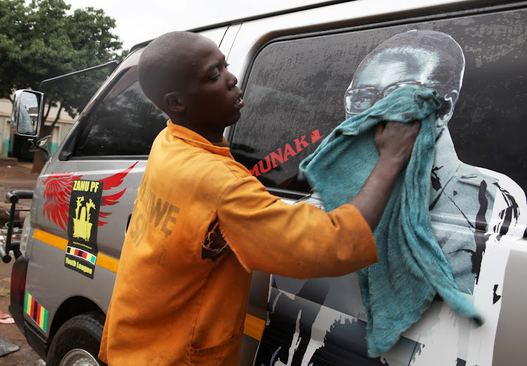 A man washes a minibus adorned with picture of President Robert Mugabe at a bus terminus in Harare, Zimbabwe, on November 15, 2017.