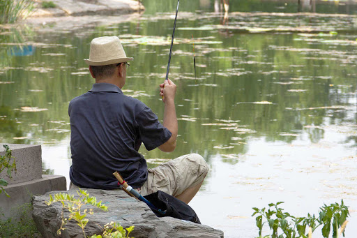 Beijing-fishing - A man fishes in a pond in Beijing, China
