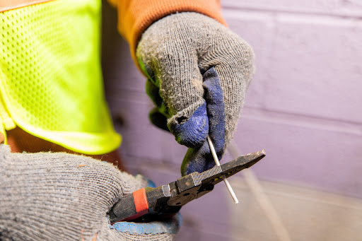 Image of hands with electric gloves, pliers and a wire