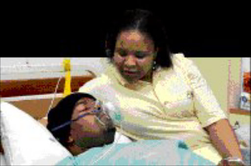 CARING WIFE: Tebogo at her husband's bedside in hospital. Vuyo Mokoena was diagnosed with a brain tumour last Thursday. His family has asked South Africans to pray for him. Pic. Antonio Muchave. 14/05/08. © Sowetan.