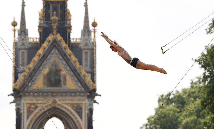 A trapeze artist practises her routine near the Albert Memorial in Hyde Park, London.