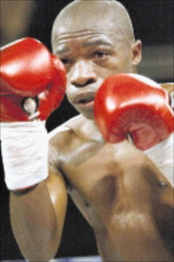 SECUNDA, SOUTH AFRICA: 24 September 2004. South African Flyweight & vacant WBC International title fight between SA champion Ngubela Gwazela (white trunks) and Moruti Mthalane (white trunks with strips) at Graceland Hotel Casino and Country Club in Secunda, South Africa Pictured here is Moruti Mthalane Photo by Lee Warren Gallo Images
