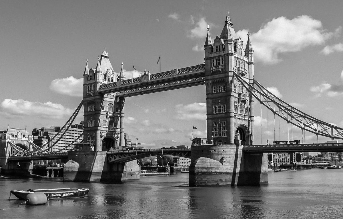 Photo: Tower Bridge In Black And White Playing with DXO Filmpack 3.  A week or so ago I posted a version of this shot to the +UK Photography Community!!!!!! BLUE SKIES + FABULOUS WEATHER SPOTTED IN THE UK !!!!! event album. I disclosed then that I had removed a small boat (lower left corner) and 'fixed' the reflection of the North Tower. In looking for a candidate photo to play with my new DxO Labs filters, I saw an opportunity with this scene.  The previous post ( http://goo.gl/1sIWl ) was processed using an older Camera Raw version, so besides playing with the filters, it was a chance to see if I couldn't clean things up better with newer tools. That done, I first used DxO Viewpoint to reduce, but not remove altogether, the keystone effect that resulted from photographing the bridge from this vantage point. I think that came out rather natural looking.  After that I took the picture into DxO FilmPack3 and chose the Fuji Neopan Acros 100 filter. I couldn't tell you if my life depended on it whether this resembles a frame shot on that film; I just liked the way it converted the scene into black and white.  #Travel  #TowerBridge  #London  #LondonUK  #BlackAndWhite  #Monochrome