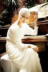 rokende vrouw in witte jurk achter een piano