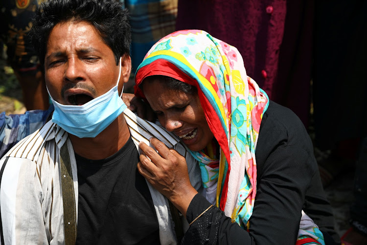 Relatives mourn after several people died as a ferry collided with a cargo vessel and sank on Sunday in the Shitalakhsyaa River in Narayanganj, Bangladesh, April 5, 2021.