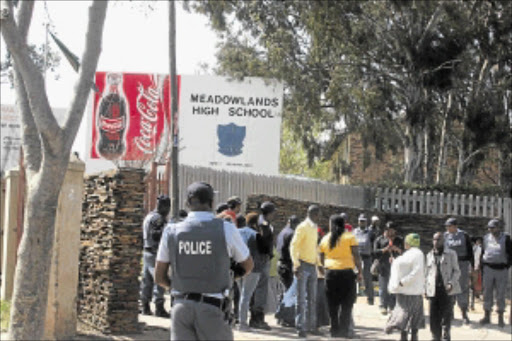 KEEPING WATCH: Police monitor the situation at Meadowlands High School in Soweto after pupils went on the rampage last year in protest over the suspension of their principal, Moss Senye. PHOTO. Bafana Mahlangu