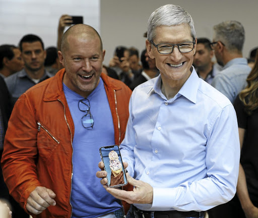 Apple CEO Tim Cook, right, plays with an iPhone as Apple chief design officer Jonathan Ive looks on during a launch event in Cupertino, California, US, on September 12 2017. Picture: REUTERS
