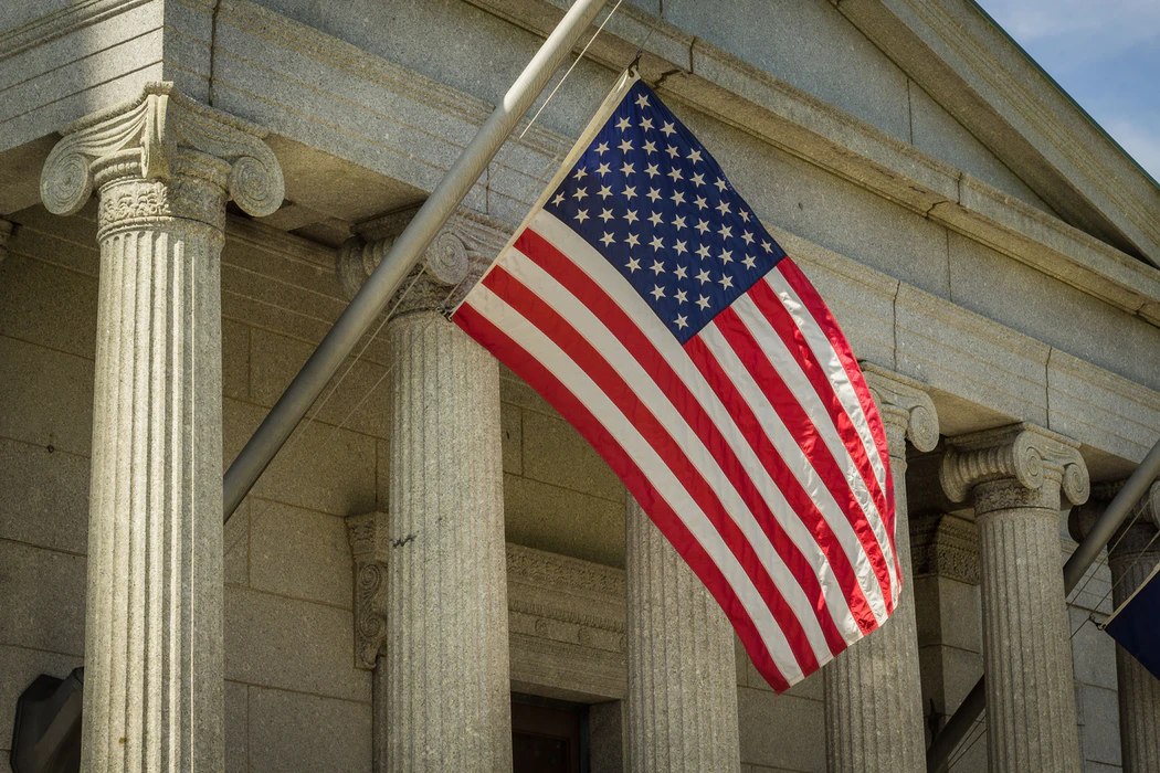 An American flag flying outside of a court building