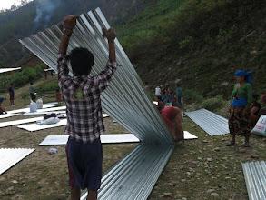 Photo: Familias recogiendo láminas de metal en la aldea de Khalte, distrito de Dhading.