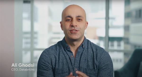 Ali Ghodsi, CEO do Databricks, sentado em frente à câmera usando uma camisa cinza com janelas ao fundo