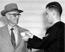 Photo: Airman Griff Davies, of New York Mills, NY pins an ID tag on Earl Hunt, owner of Hunt Auto Comany, in conjuncton withh the Beeville Navy League visit to the base on Dec. 11, 1958