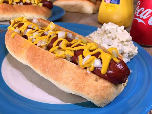 A Hot Dog On A Plate With Potato Salad.