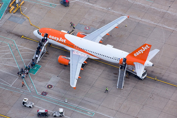 Passengers board an Airbus A320 passenger aircraft, operated by Easyjet Plc, at London Gatwick airport in this aerial view taken over Crawley, UK. Picture: Bloomberg/Jason Alden