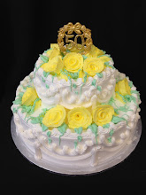 Photo: Classic 2-tier stacked cake featuring yellow whipped cream roses w/light green foliage, Lisa's traditional border, and a gold 50th anniversary topper.