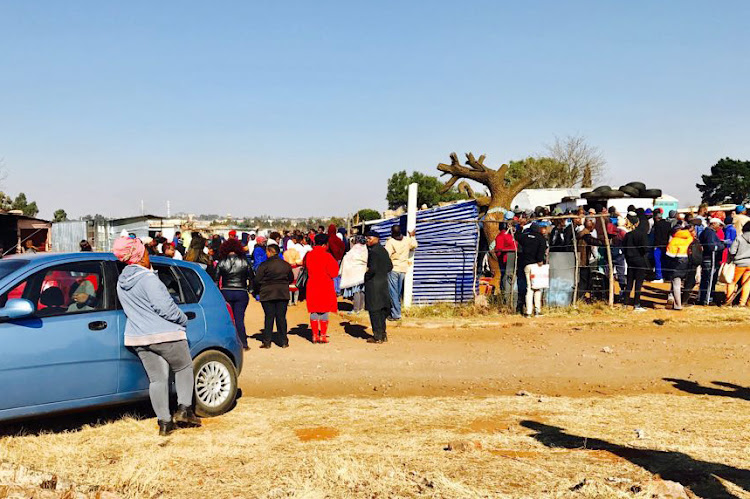 People queue with their ID documents to be registered by members of the EFF for a piece of land in Brakpan on June 22 2018
