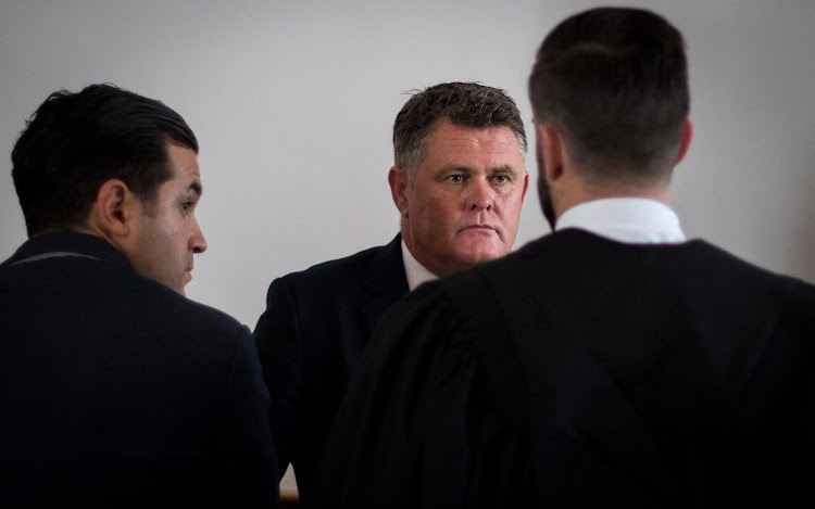 Murder accused Jason Rohde speaks with his defense team in court before day four begins.