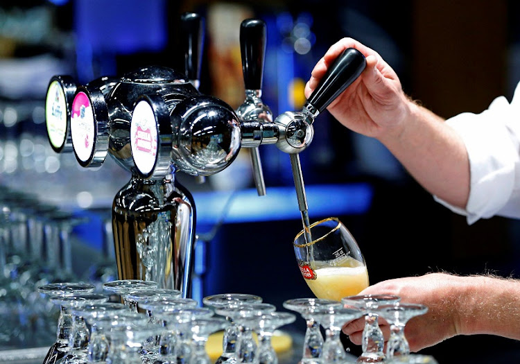 A waiter serves a glass of beer ahead of an Anheuser-Busch InBev shareholders meeting in Brussels in this April 30 2014 file photo. Picture: REUTERS