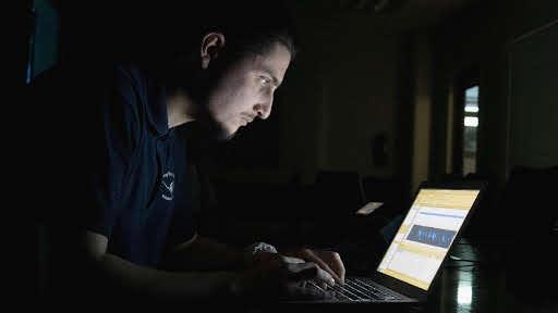 Daniel DeLeon mientras usa un software de aprendizaje automático para identificar cantos de ballenas desde un feed de audio del océano