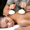 a lady receiving a thai hot herbal compress massage