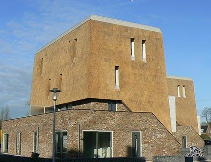 Kwadratowy dom ze scianami pokrytymi trzciną i wąskimi długimi oknami