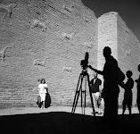 vrouw wordt gefotografeerd, staand voor een oud-Egyptische muur met dierenfiguren