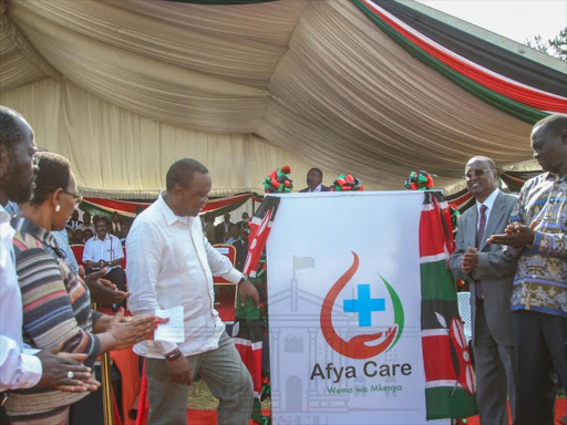 President Uhuru Kenyatta unveils the UHC logo during the launch of the pilot programme in Kisumu on December 13
