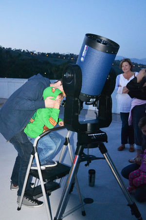 Child and student looking through telescope