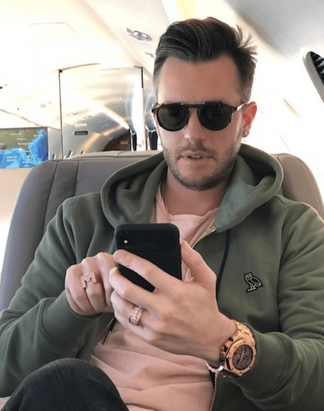 photo of adrian morrison sitting on a private jet using his cellphone