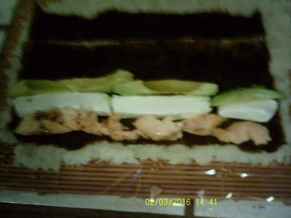 Place salmon, cream cheese, and avocado slices in thin rows on top of nori...