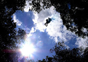 An adventurer souring above the tree tops at Karkloof Canopy Tours.