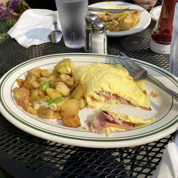 Beakfast at a sidewalk table. Ham & cheese omelette with potatoes.