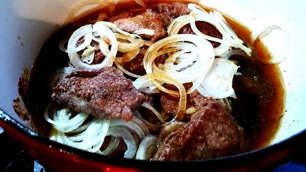 Once steak is browned, layer with onions in same pan. Add water, broth, Worcestershire...