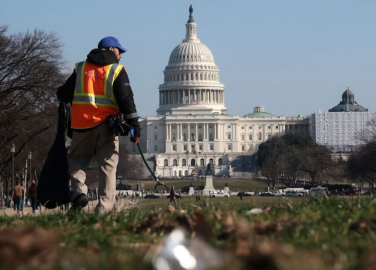 A worker picks up trash on January 6 2019 on the National Mall near the US Capitol building in Washington as the partial US government shutdown continues. Picture: REUTERS/Jim Young