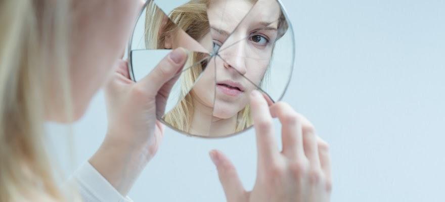 Kobieta z borderline patrzy na odbicie w lustrze w trakcie terapii