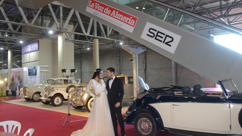 Novios ante vehículos clásicos en Expoboda.