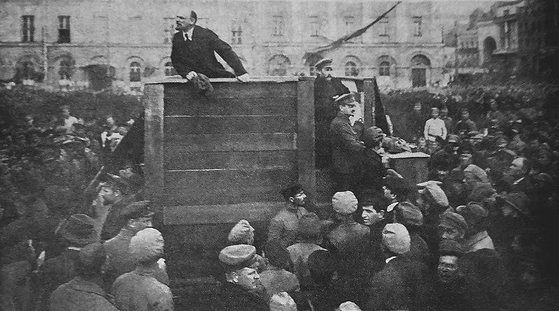 Lenin standing on a platform giving a speech to a crowd.