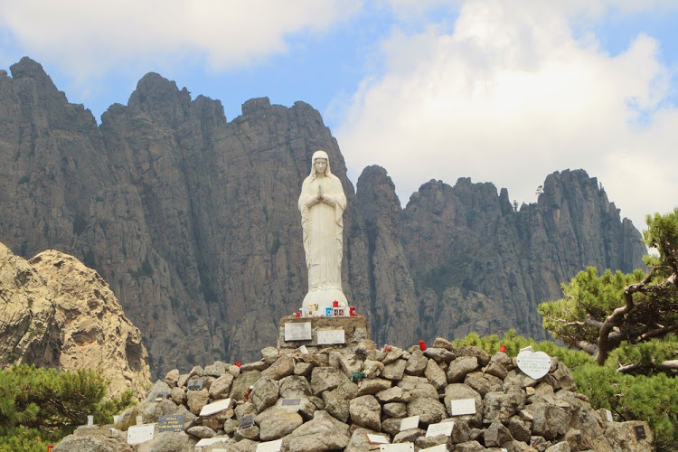 A statue of Our Lady of the Snows stands next to the road at the Col de Bavella mountain pass and is framed by the needle-shaped granite of the Aiguilles de Bavella in Corsica