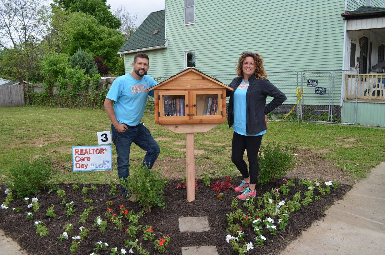 man and woman standing by a Little Free Library in a yard